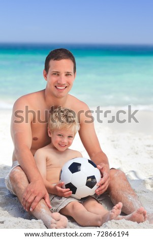 Son playing football with his father - stock photo