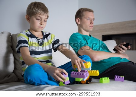 Son playing the blocks alone on the couch in lounge - stock photo