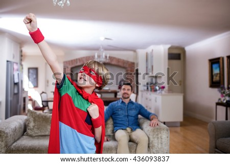 Son pretending to be a superhero while father sitting on sofa at home - stock photo