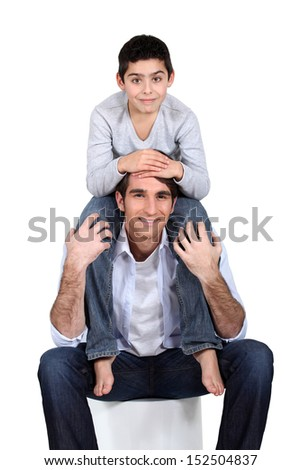 Son sat on father's shoulders - stock photo