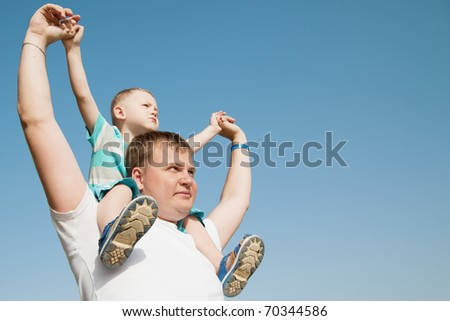 Son sits on father's shoulders and they look to the side, against the blue sky - stock photo