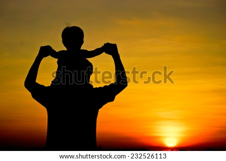 son sitting on his father's neck silhouette - stock photo