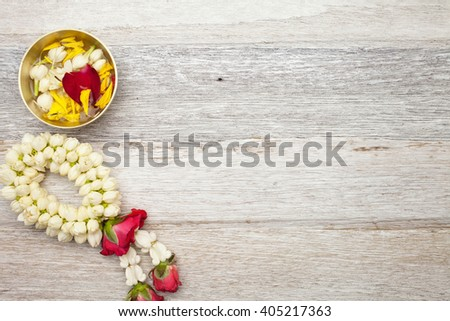 Songkran Festival : Garland and floral on white wooden background - stock photo