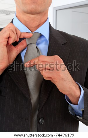 Sophisticated businessman adjusting his tie - stock photo