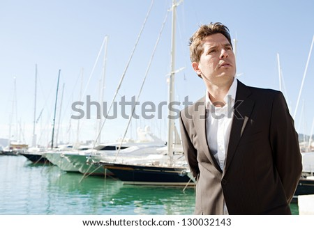 Sophisticated businessman standing on a marine with sailing boats in the background, being thoughtful against a blue sky. - stock photo