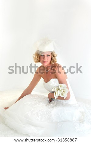 Sophisticated hat with white netting adds charm to beautiful bride reclining on white carpet.  Calilillies lay across her arm. - stock photo