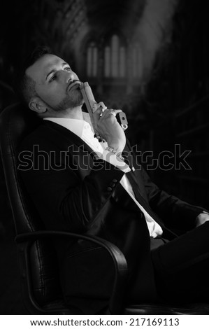 Sophisticated young man agent police killer hitman assassin sitting in a chair holding a gun against his lips black and white portrait - stock photo