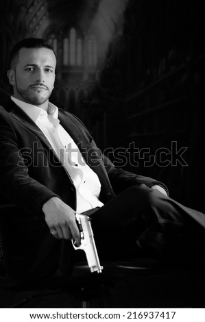 Sophisticated young man agent police killer hitman assassin sitting in a chair holding a gun over dark background black and white portrait - stock photo