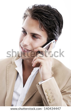 Sophisticated young man smiling while talking on the phone on a white background - stock photo