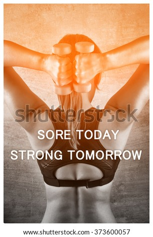 Sore today strong tomorrow. Inspiration quote. Fit woman exercising with weights on the background of a concrete wall in the gym. Healthy lifestyle concept. - stock photo