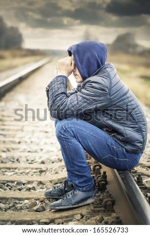 Sorrowful boy on the railway - stock photo