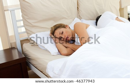 Sorrowful couple lying in the bed after having an argument - stock photo