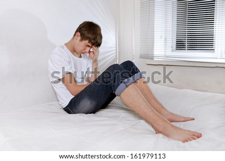 Sorrowful Young Man sitting on the bed Alone - stock photo