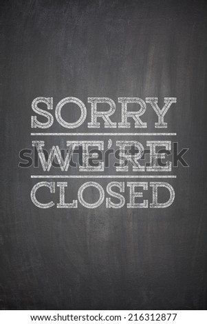 Sorry we're closed on black blackboard - stock photo