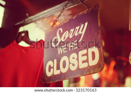 Sorry we're closed sign.  grunge image hanging on a dirty glass door. - stock photo