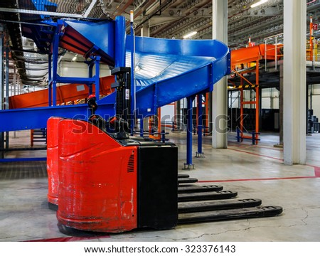 Sorting line for cargo in large modern warehouse with forklifts - stock photo
