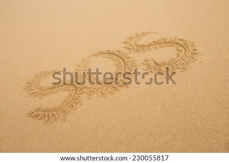 SOS - Inscription on the sand of tropical beach  - stock photo