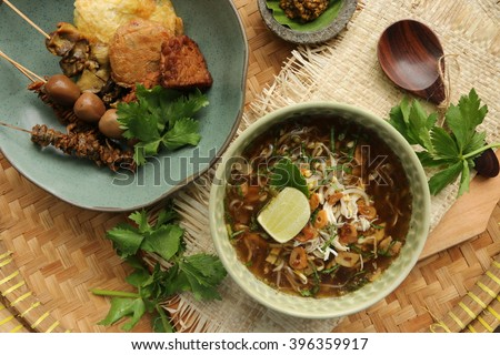 Soto Kudus, Indonesian chicken soup from Kudus, Central Java. Served with complete accompaniments and green chili paste. Arranged on traditional woven bamboo tray. - stock photo
