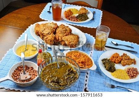 Soul Food dinner -- southern fried chicken with collard greens, black eyed peas; creamed corn and candied yams set on vintage oak table. - stock photo