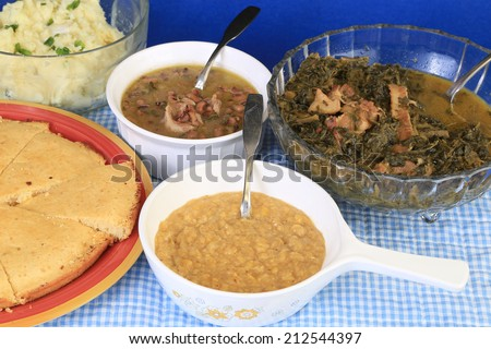 Soul Food Supper served family-style on blue gingham background -- creamed corn; black-eyed peas; collard greens; mashed potatoes and corn bread. - stock photo