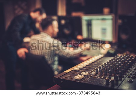 Sound engineer and producer working together at mixing panel in the boutique recording studio. - stock photo