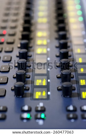 Sound mixer, professional audio mixing console with yellow, green, red lights and buttons  - stock photo