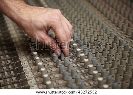 sound producer rotating a regulator of old dirty sound mixer panel - stock photo