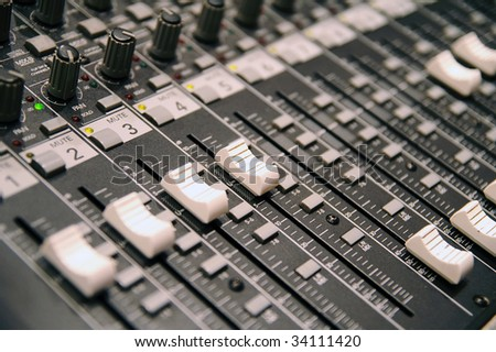 Sound-recording control desk with sliders and knobs, close up, blur, shallow depth - stock photo