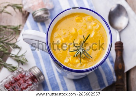 Soup-cream of corn with curry paste and rosemary, in a mug. - stock photo