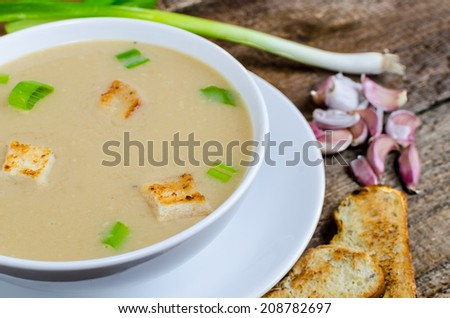 Soup garlic with toasted croutons on wood table - stock photo