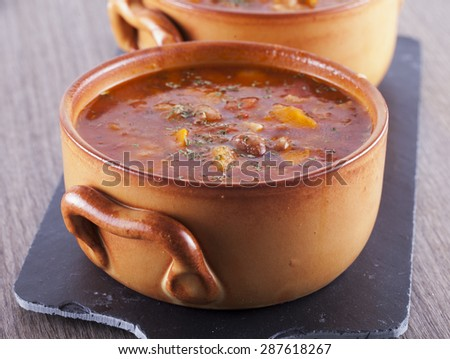 Soup in clay bowl over black stone chopping board, horizontal image - stock photo