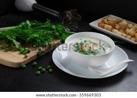 soup of peas , fresh petrshka , dill , toast , green peas, cutting board, blender - stock photo