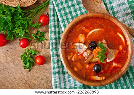 Soup solyanka Russian with meat, olives and gherkins in wooden bowl - stock photo