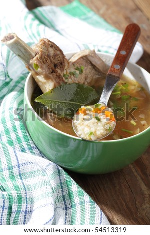 Soup with beef rib on a rustic table - stock photo