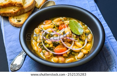 Soup with different vegetables, cannellini beans, cavolo nero, bread.Famous typical tuscan soup, ribollita.Plate with soup. - stock photo