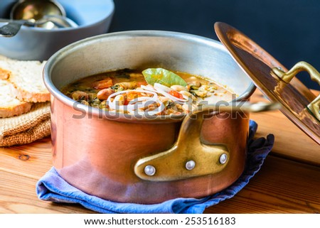 Soup with different vegetables, cannellini beans, cavolo nero, bread.Famous typical tuscan soup, ribollita. - stock photo