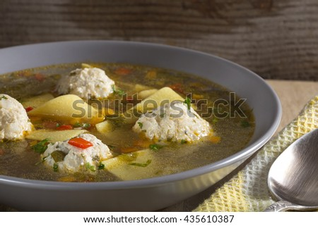 Soup with meatballs and noodles in plate over wooden background - stock photo