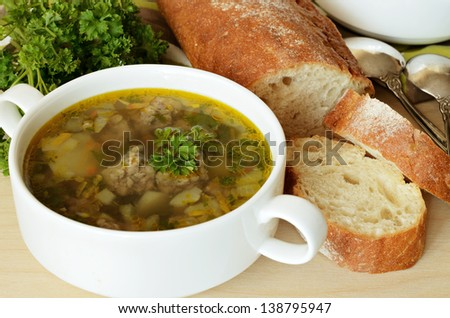 Soup with meatballs served with bread - stock photo