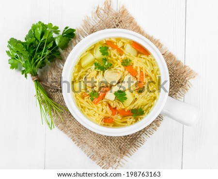 Soup with noodles and chicken in a white ceramic bowl - stock photo