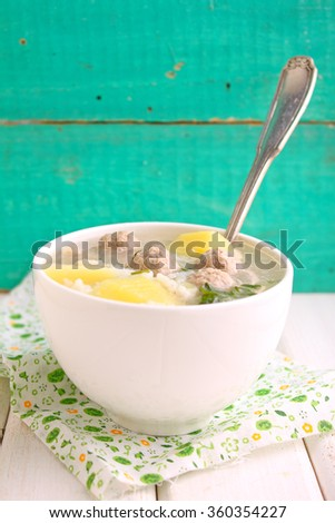 soup with potatoes, rice and meatballs in a white cup on a bright background - stock photo