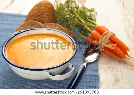 Soup with pumpkin and carrot on a blue tablecloth in country style - stock photo