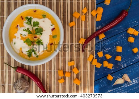 Soup with pumpkin and cream. On a blue wooden background. Top view - stock photo