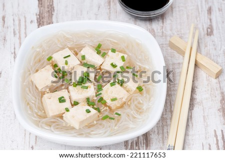 soup with rice noodles, tofu and green onions, top view, close-up - stock photo