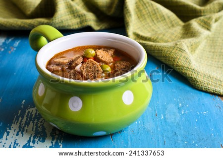 Soup with small pasta, vegetables and croutons in a ceramic bowl on a wooden surface - stock photo