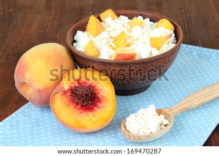 Sour cheese and fresh peaches,on wooden table background - stock photo