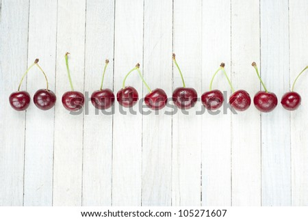 sour cherries in a row on white wooden table - stock photo
