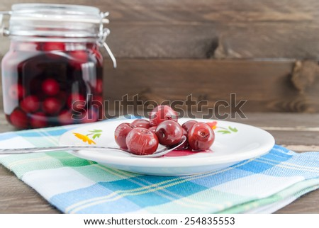 Sour cherries on spoon and in the background the jar with sour cherry compote - stock photo