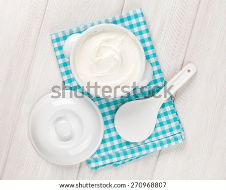 Sour cream in a bowl on wooden table. Top view - stock photo