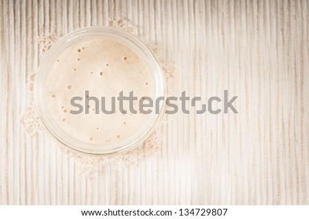 Sourdough in a glass jar on a cream striped table mat with a doily,  top view - stock photo