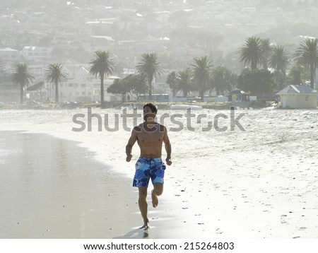 South Africa, Cape Town, man in swimming shorts jogging along sandy beach - stock photo